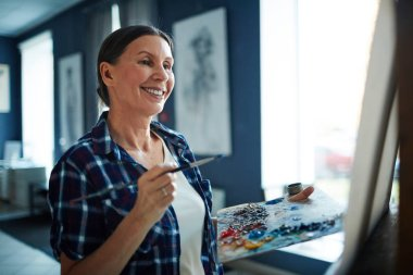 Mature woman painting picture