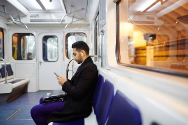 Businessman using smartphone in metro