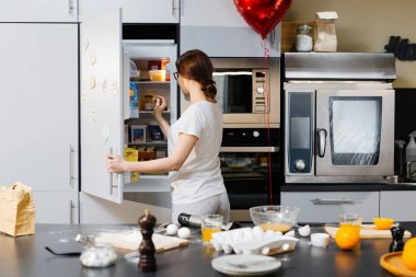 woman taking products from fridge