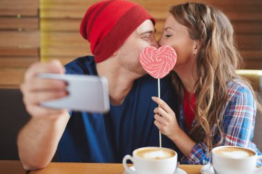 couple making selfie while kissing