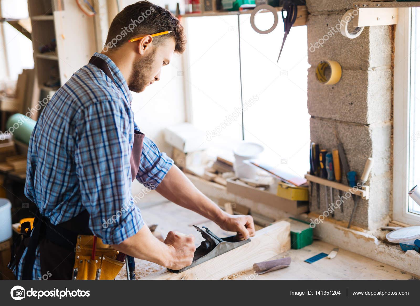 Carpenter planing wood on workbench — Stock Photo