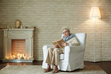 woman in eyeglasses reading exiting book