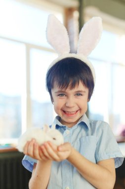 Smiling boy with white rabbit