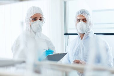 colleagues in eyeglasses, gloves and respirators