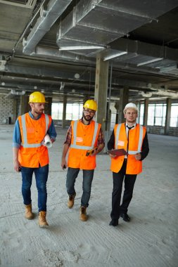 Group of three workmen wearing protective helmets and vests walking among concrete walls of unfinished building showing development progress to foreman inspector on construction site stock vector