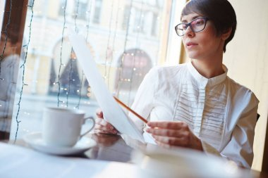 Businesswoman Reviewing Contracts in Cafe