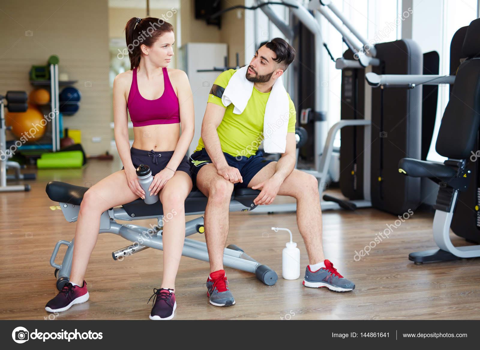 569daf199aee Giovane e donna sia indossando abbigliamento sportivo brillante che si  siede sulla panca regolabile che riposa dopo l'allenamento con macchine e  guardando ...