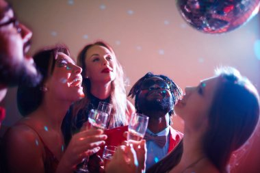 friends with champagne looking at disco ball