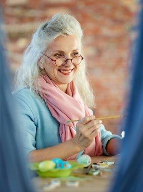 Senior female painting eggs