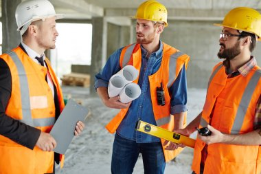 Group of three workmen wearing protective helmets and vests standing among concrete walls on construction site discussing development progress with inspector, holding tools and blueprints stock vector