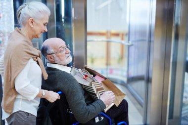 Senior spouses entering shopping-center
