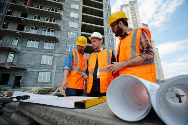 Low angle portrait of two workmen showing apartment building blueprints to inspector on construction site, all wearing reflective orange vests and hard hats stock vector