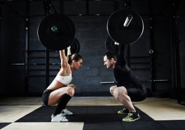 man and woman holding  huge barbells