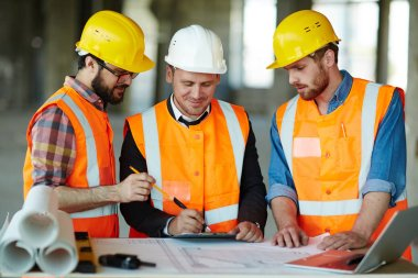 Team of construction workers wearing protective helmets and vests discussing project details with executive supervisor standing at table with blueprints, tools and laptop on it stock vector