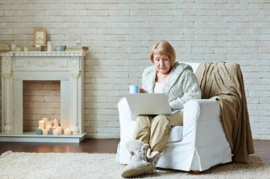 woman in armchair using laptop