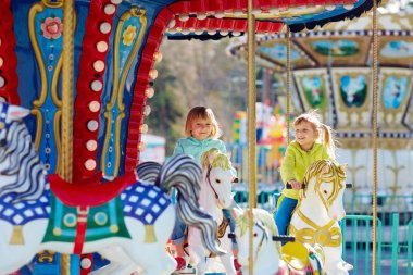 girls riding on merry-go-round
