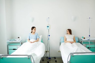 Two pregnant women resting in beds