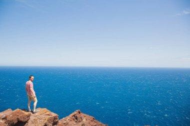 male traveler standing on cliff