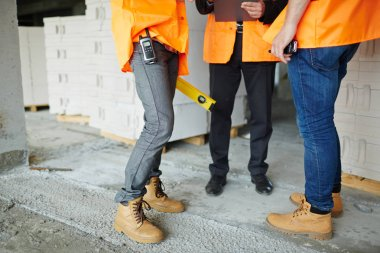 Low section shot of legs of two construction workers wearing jeans and brown leather work boots standing with man in suit on concrete floor stock vector