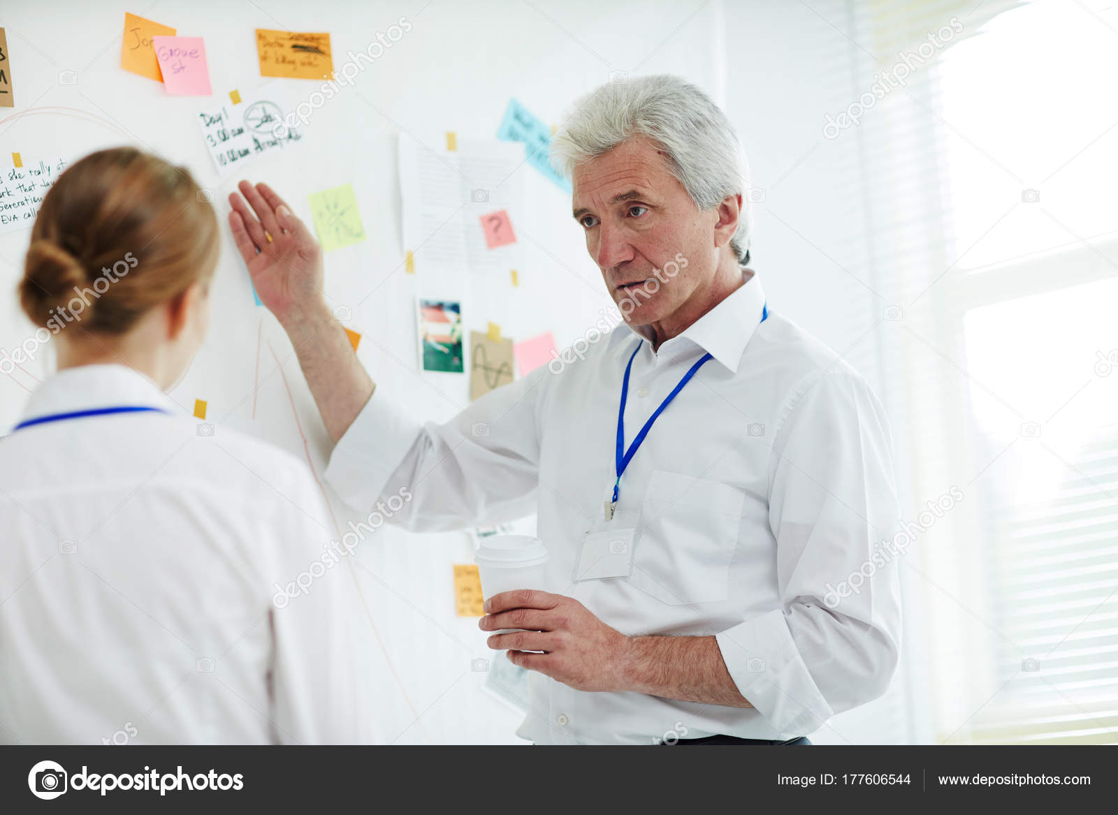Confident Mature Private Investigator And His Young Assistant Gathered Together At Investigation Board Making Assumptions About Possible Motives Of