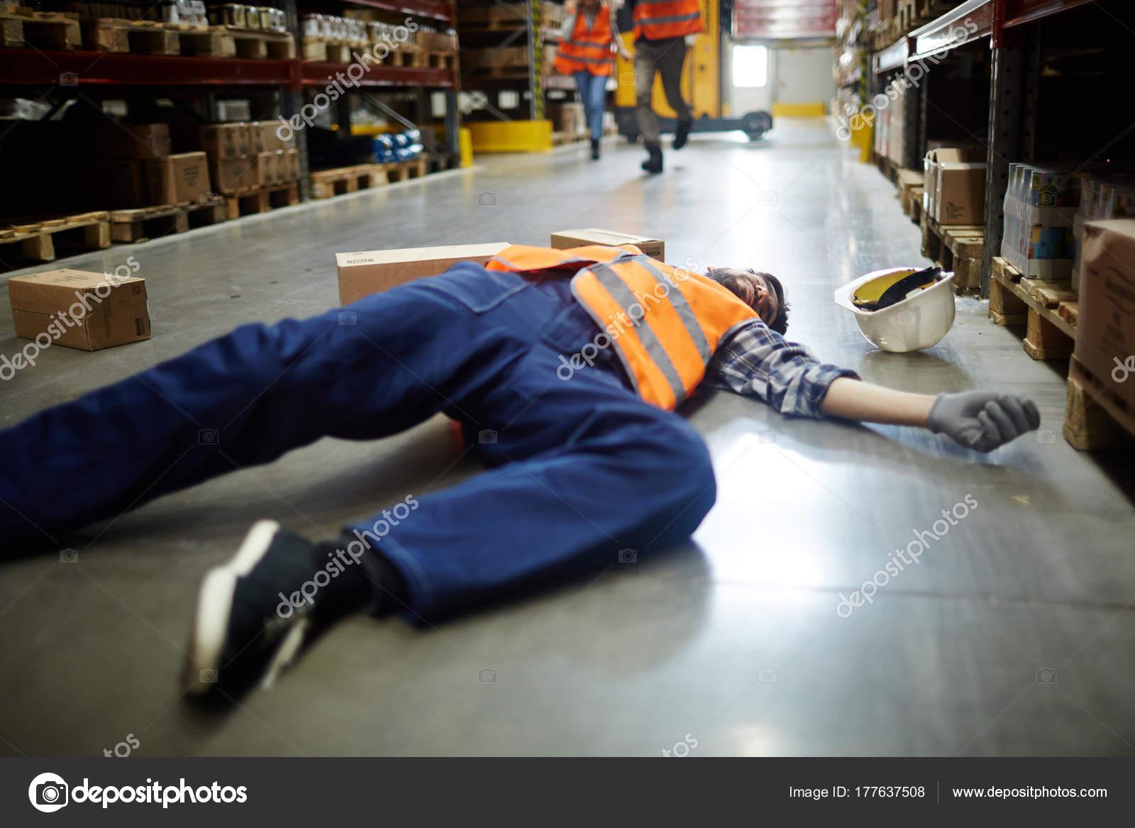 Trabajador ca do tendido suelo pasillo entre estanter as - Estanterias de almacenaje ...