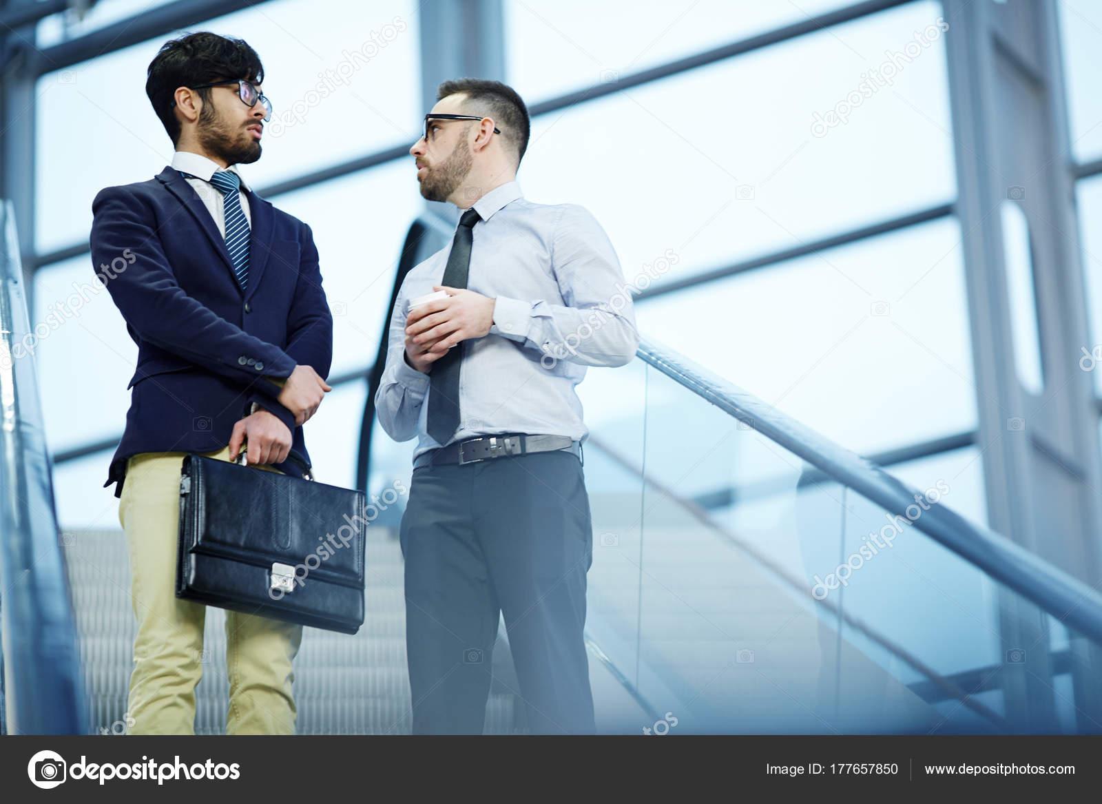 Porträt Von Zwei Geschäftsleute Sprechen Lässig Auf Der Rolltreppe ...