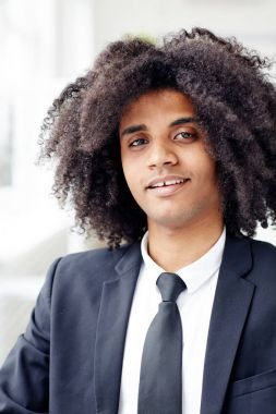Confident businessman with wavy hair looking at camera