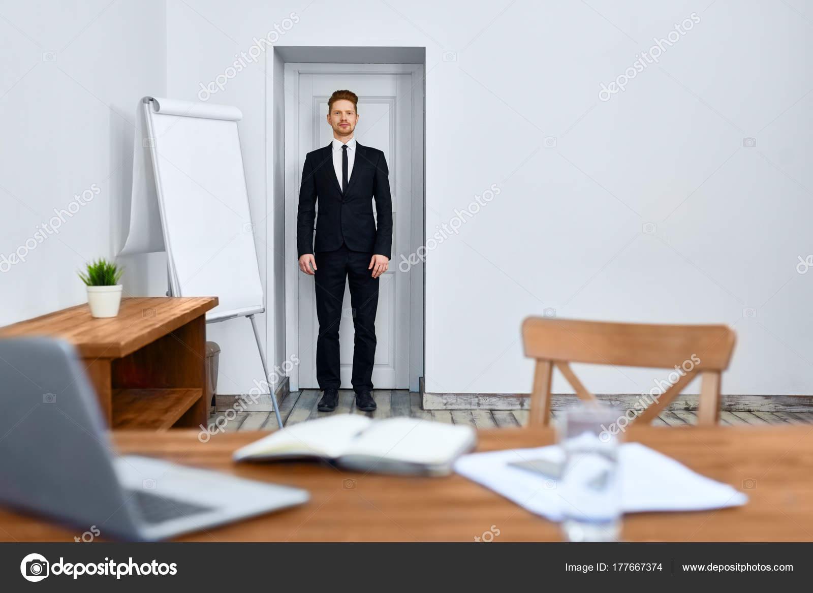 Vestito Elegante Ufficio : Uomo serio vestito elegante piedi dalla porta dell ufficio chiuso