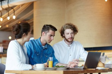 Group of students preparing coursework or joint project in front of laptop