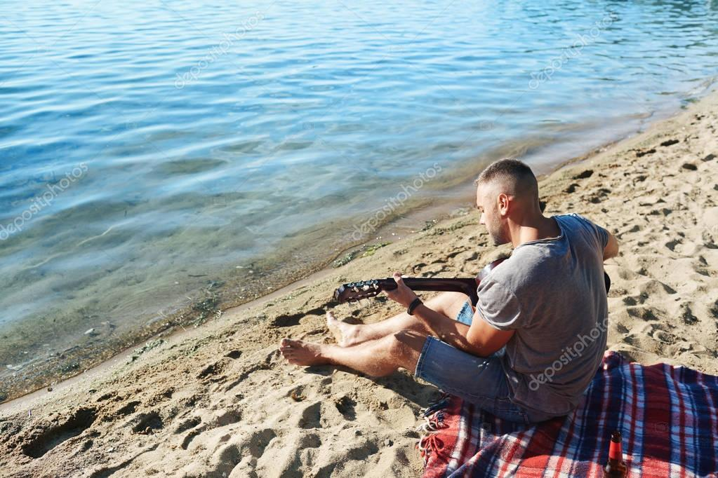 Young man playing guitar while relaxing on sandy beach