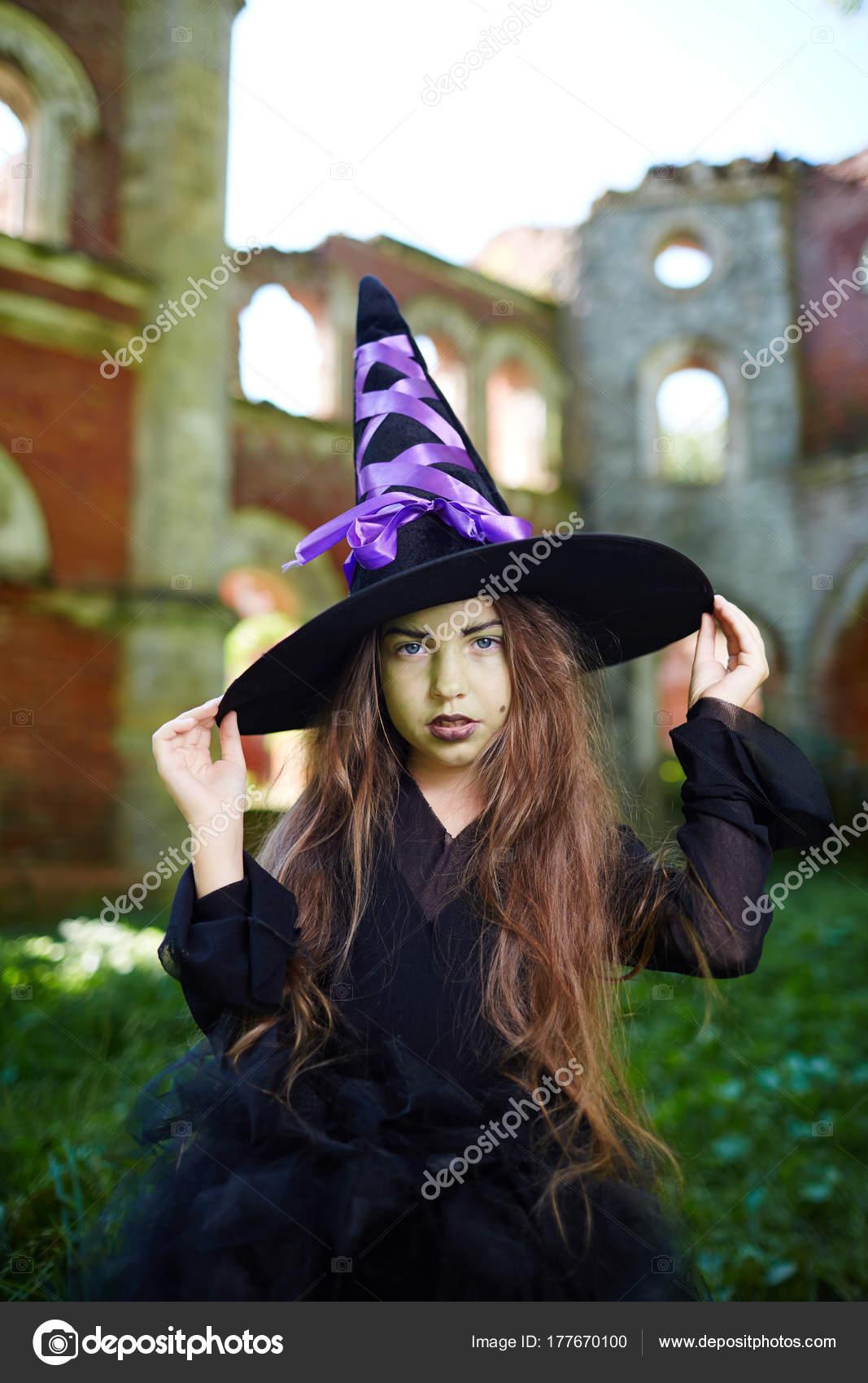 Linda garota com cabelo comprido usar vestido preto e chapéu de bruxa 0b1b7628f84