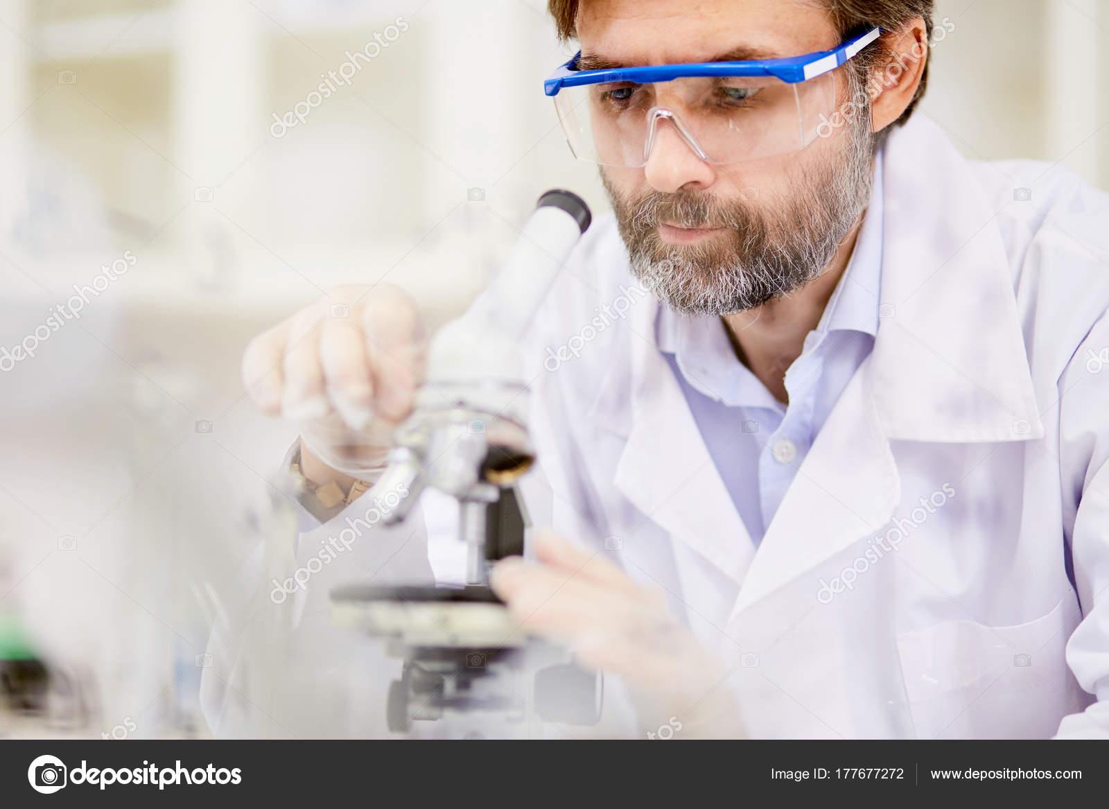Confiant chercheur barbu portant des lunettes de sécurité réglage de  microscope pour examiner la substance chimique, arrière-plan flou — Image  de ... eac7f31bc869