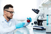 Side view portrait of focused researcher performing blood tests in modern medical laboratory using microscope