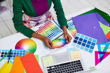 Workplace of creative designer with various color swatches and hands of specialist at work