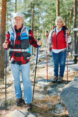 Active senior man with trekking sticks looking at camera wit his wife on background