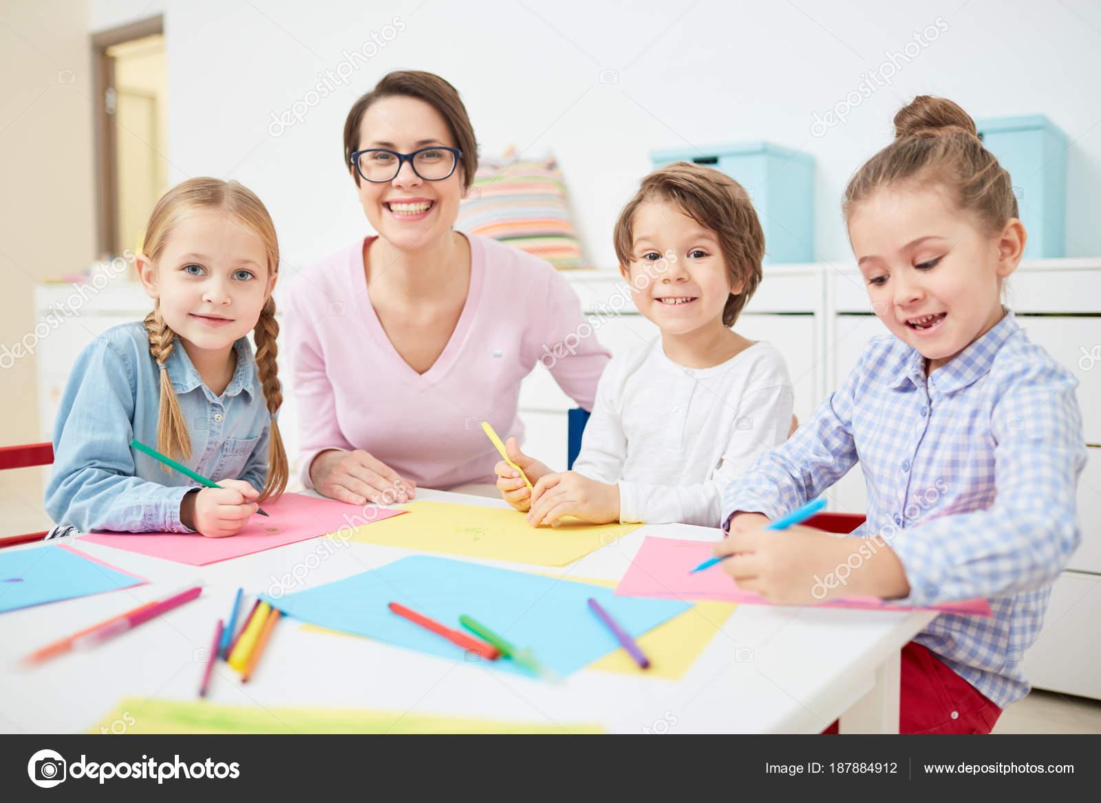 Mutlu Genç öğretmen Küçük Grup çok Güzel çocuk Anaokulunda Boya