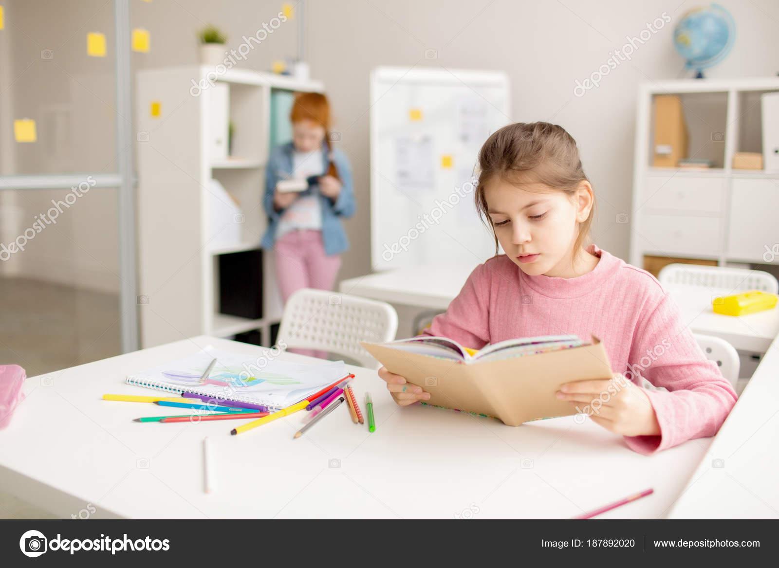 61cccc607514 Σοβαρή μαθήτρια ανάγνωση ενδιαφέρον βιβλίο στη βιβλιοθήκη του σχολείου