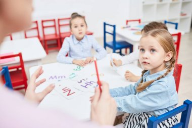Attentive lementary schoolgirl listening to explanation of teacher at lesson of english language