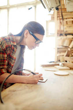 Young female carpenter with pyrographic equipment drawing ornaments on wooden board