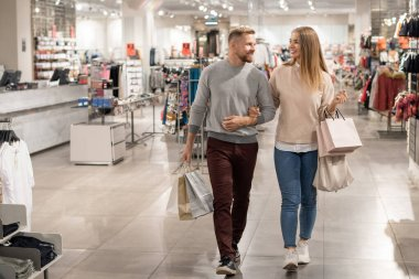 Young shoppers with paperbags leaving casualwear department after buying new clothes to go on shopping in the mall