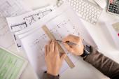 Přehled rukou inženýra nebo architekta s tužkou a kreslicí čárou pravítka při práci na náčrtku po stole
