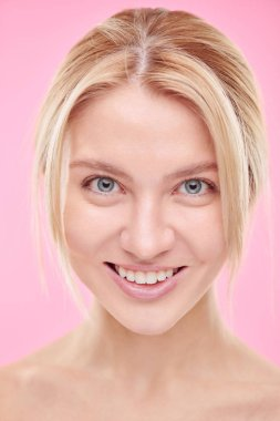 Young beautiful smiling woman with natural makeup looking at camera in isolation against pink background