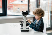 Clever little scientist putting chemical sample in microscope while going to study new elements in laboratory