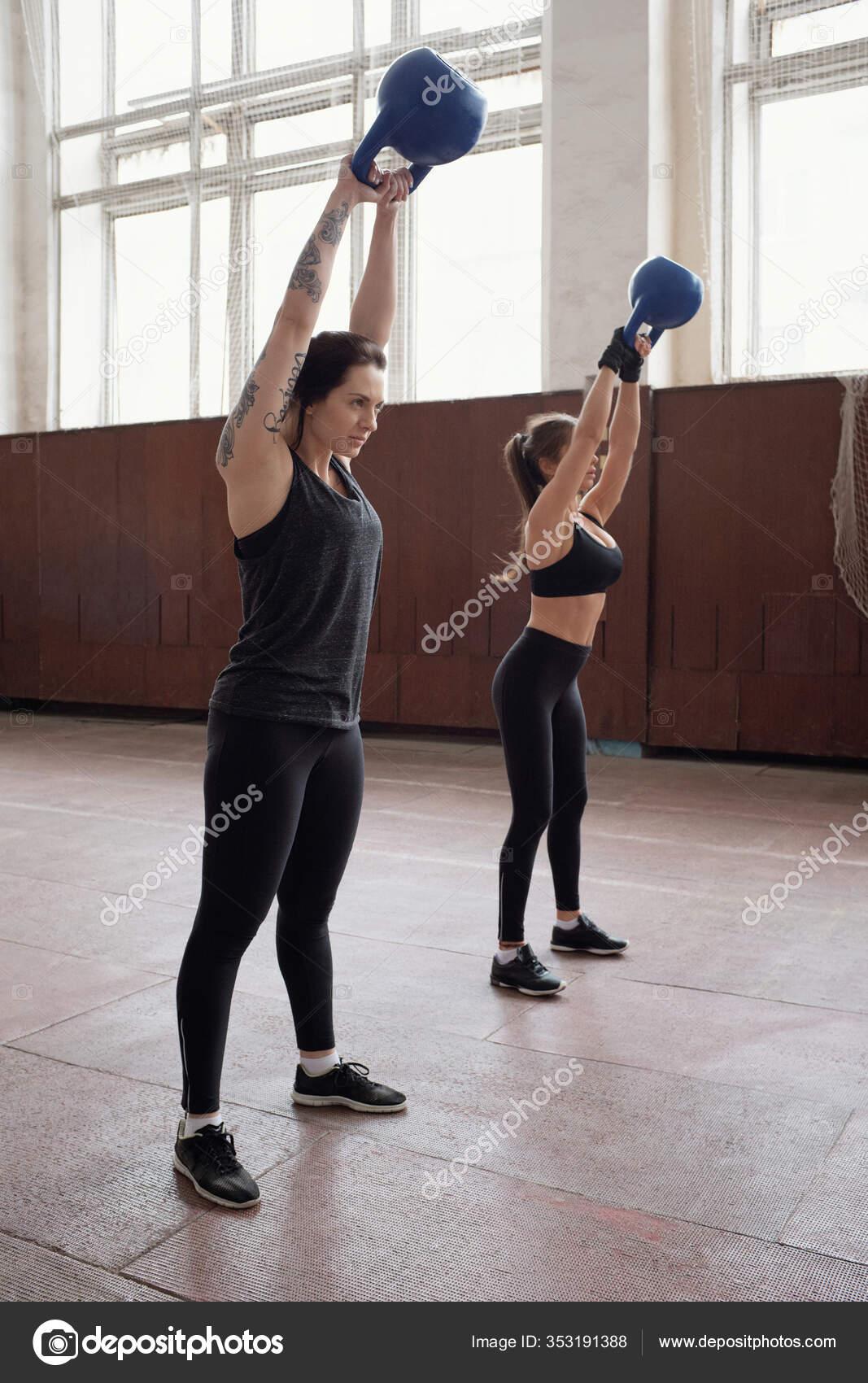 Young Athletic Women Black Sportswear Doing Exercise Kettlebells While  Having — Stock Photo © pressmaster #353191388