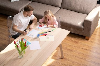 Cute little girl drawing house on paper with crayons or highlighters while her father sitting near by and consulting her