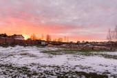 ein flaches Grundstück, das im Winter mit einem schönen rosafarbenen Sonnenuntergang versteigert wird