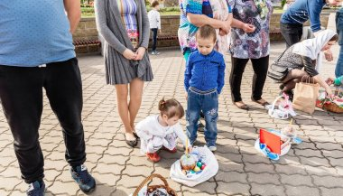 Beryoza, Belarus - April 27, 2019: The children have come to the church and are waiting for the priest to sprinkle them and their Easter basket with Easter cakes and colored eggs. Christian religious tradition.