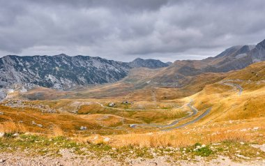 Rocky mountains covered with autumn meadow against the background of a stormy sky
