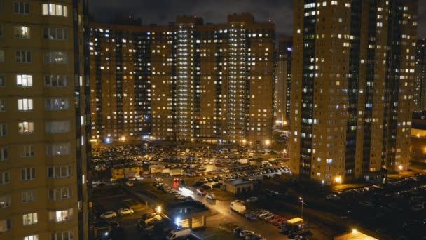 Pohled z okna domu a parkování ve večerních hodinách ve velkém městě. Lidé se vrátit domů po celodenní práci. Systému windows se rozsvítit. Timelapse
