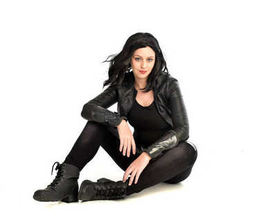 full length portrait of black haired girl wearing leather outfit.  seated on pose, isolated on a white studio background.